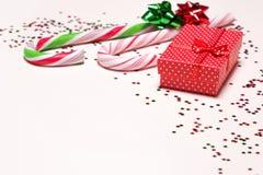 Primer de la caja de regalo con los bastones de caramelo y el confeti Fotos de archivo