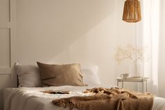 Primer de la cama con la manta beige y la almohada de lino en el interior mínimo del dormitorio, foto real imagenes de archivo