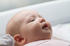 Primer de la cara linda del bebé Bebé que miente en su cama maternidad Imágenes de archivo libres de regalías