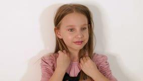 Primer de la cara de la niña en pelo largo en estudio en el fondo blanco almacen de metraje de vídeo
