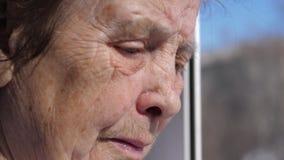 Primer de la cara triste de una mujer mayor que sufre del temblor que sacude los párpados almacen de video
