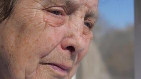 Primer de la cara triste de una mujer mayor que sufre del temblor que sacude los párpados almacen de metraje de vídeo
