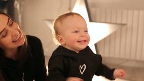 Primer de la cara de un pequeño bebé rubio en un fondo brillante almacen de metraje de vídeo