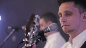 Primer de la cara y del micrófono del músico El artista canta en el micrófono en etapa almacen de metraje de vídeo