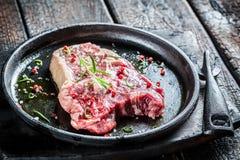 Primer de la carne de vaca con el romero y la pimienta listos para asar a la parrilla Imagen de archivo