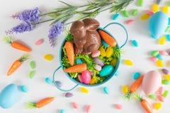 Primer de la cesta de Pascua con el conejito del chocolate, las mini zanahorias, y los huevos de caramelo en el fondo blanco fotos de archivo