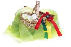 Primer de la cesta strawy aislada en el fondo blanco con los huevos de Pascua Imagen de archivo libre de regalías