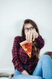 Primer de la chica joven que come la pizza Imagen de archivo