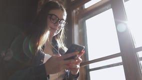 Primer de la chica joven que manda un SMS en el teléfono almacen de metraje de vídeo