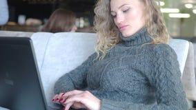 Primer de la chica joven que usa el ordenador portátil para el trabajo remoto sobre fondo de la ventana, tecnología y red social metrajes