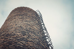 Primer de la chimenea del ladrillo de la fábrica Contaminación atmosférica por las emisiones industriales Foto de archivo