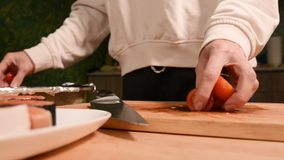 Primer de la cocina de las manos de la muchacha en casa en tomates de una cereza de los cuchillos de madera de la tabla de cortar almacen de video