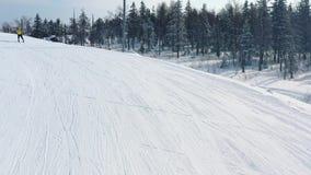 Primer de la cuesta del esquí y hombre en el esquí de la chaqueta amarilla en una pista cerca del bosque conífero en invierno can metrajes