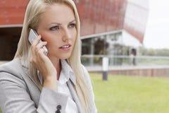 Primer de la empresaria joven que conversa en el teléfono móvil contra el edificio de oficinas Foto de archivo