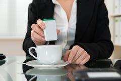 Primer de la empresaria Putting Sugar In Cup foto de archivo libre de regalías