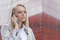 Primer de la empresaria rubia que conversa en el teléfono móvil con el edificio de oficinas en fondo Foto de archivo
