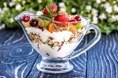 Primer de la ensalada de fruta con las bayas, el yogur y el granola en un arco de cristal Foto de archivo libre de regalías