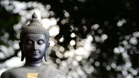 Primer de la estatua de Buda con el fondo de la luz del bokeh foto de archivo