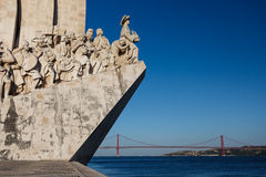 Primer de la estatua de los navegadores en el río Tagus con el puente del retén del cable en el fondo en Lisboa, Portugal Fotografía de archivo libre de regalías