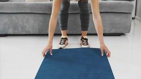 Primer de la estera azul compleja femenina de la yoga o de la aptitud después del trabajo en casa en la sala de estar almacen de metraje de vídeo