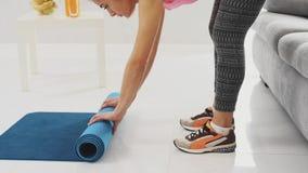 Primer de la estera azul compleja femenina de la yoga o de la aptitud después del trabajo en casa en la sala de estar almacen de video