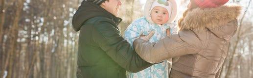 Primer de la familia joven feliz que pasa el tiempo al aire libre en invierno Imagen de archivo libre de regalías
