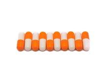 Primer de la fila anaranjado-blanca de las píldoras Imágenes de archivo libres de regalías