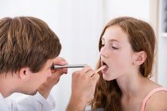 Primer de la garganta del ` s del doctor Examining Girl foto de archivo