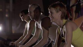 Primer de la gente joven sonriente en el centro de aptitud que ejercita en las bicis inmóviles modernas almacen de video