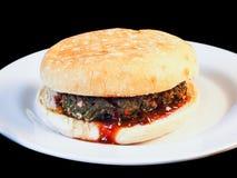Primer de la hamburguesa jugosa entre los bollos Imagen de archivo libre de regalías