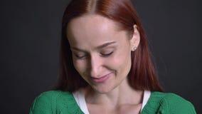 Primer de la hembra caucásica atractiva que es en cámara sonriente y de mirada avergonzada y torpe almacen de metraje de vídeo