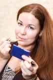 Mujer que aplica el lápiz labial rosado en los labios Imagen de archivo