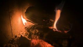 Primer de la le?a oscuro ardiente con los carbones en una estufa casera moderna detr?s de un vidrio refractario en la noche Mirad almacen de video