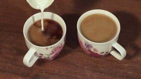 Primer de la leche que vierte en las dos tazas de café almacen de metraje de vídeo