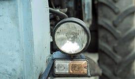Primer de la linterna en el tractor Mitad del tractor histórico verde oxidado viejo del vintage con la cerca ligera del neumático Foto de archivo