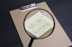 Primer de la lupa y de la etiqueta engomada 'que estamos empleando 'en el tablero del browm, fondo negro El concepto de contratar imagen de archivo libre de regalías