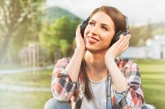 Primer de la música que escucha femenina alegre en los auriculares y el re Imágenes de archivo libres de regalías