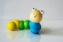 Primer de la madera, colorido, niños, oruga del juguete en los vagos blancos fotos de archivo