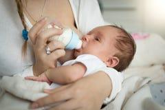 Primer de la madre que alimenta al bebé recién nacido de la botella fotografía de archivo libre de regalías