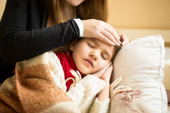 Primer de la madre que cuida que se sostiene principal en la frente enferma de la hija Imágenes de archivo libres de regalías