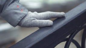 Primer de la mano de la chica joven que resbala sobre la verja Mano en los tactos grises del guante que cercan con barandilla al  fotografía de archivo libre de regalías