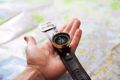 Primer de la mano con el compás magnético sobre un mapa Fotografía de archivo