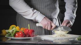 Primer de la mano con el cuchillo que corta las verduras frescas Col joven del corte del cocinero en un primer blanco de la tabla almacen de metraje de vídeo