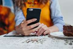 Primer de la mano de la muchacha con el teléfono Fotos de archivo libres de regalías