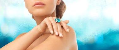 Primer de la mano de la mujer con el anillo azul grande del cóctel Foto de archivo libre de regalías