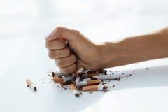 Primer de la mano de la mujer que rompe los cigarrillos Abandone el mún hábito Imagen de archivo libre de regalías
