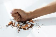 Primer de la mano de la mujer que rompe los cigarrillos Abandone el mún hábito Foto de archivo libre de regalías