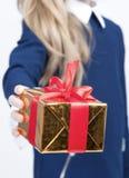 Primer de la mano de la pequeña muchacha rubia que da la caja de regalo de la Navidad adelante Foto de archivo libre de regalías