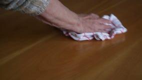 Primer de la mano de los woman's que limpia una tabla almacen de metraje de vídeo