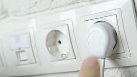 Primer de la mano de un hombre que inserta un enchufe eléctrico en un socket de pared metrajes